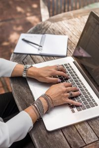 A person with bracelets typing on a laptop.