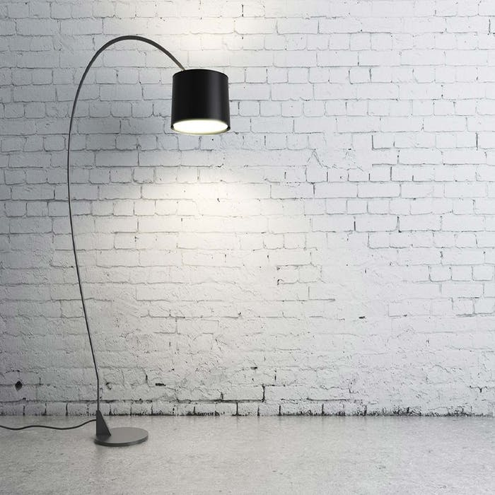 A black lamp in front of white wall
