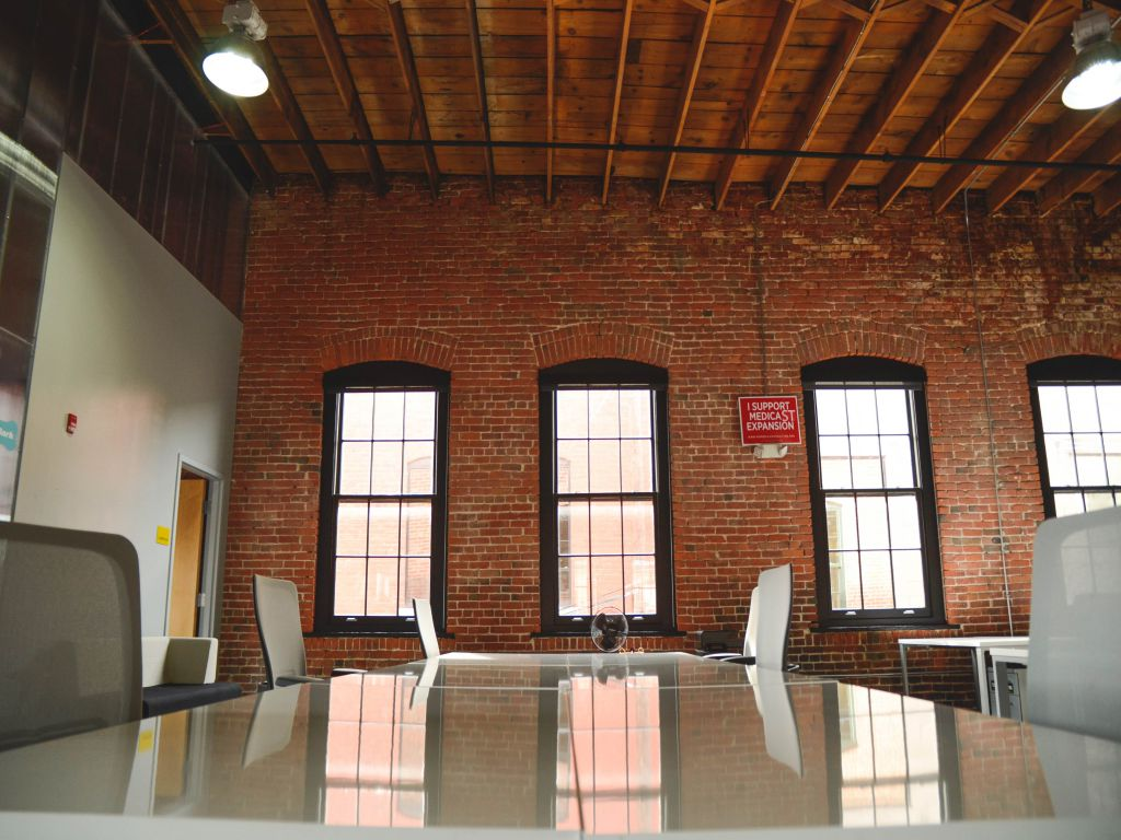 An empty office with white furniture and an exposed brick wall.