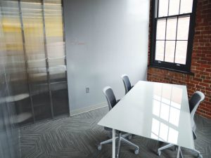 An empty office with a table and a whiteboard, representing space to check out while you prepare your office for moving day.